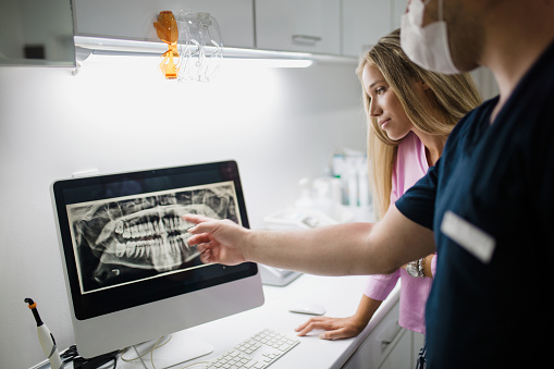 Dentist reviewing digital x-ray with assistant