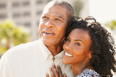 older Black couple smiling after making appointment at Mountain State Oral and Facial Surgery